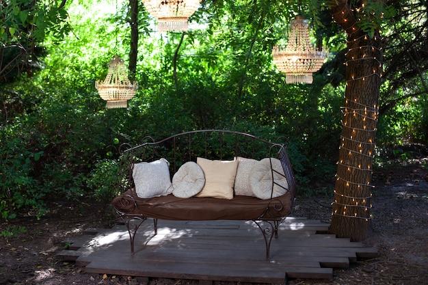 Elegancka sofa w ogrodzie, zewnętrzna kompozycja dekoracyjna z trzema żyrandolami. piękny elegancki wystrój na ślub w pięknym ogrodzie. altana do relaksu na świeżym powietrzu. romantyczna nisza