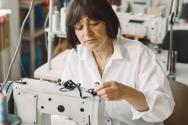 Elegancka stara kobieta siedzi w studio i szyć szmatką