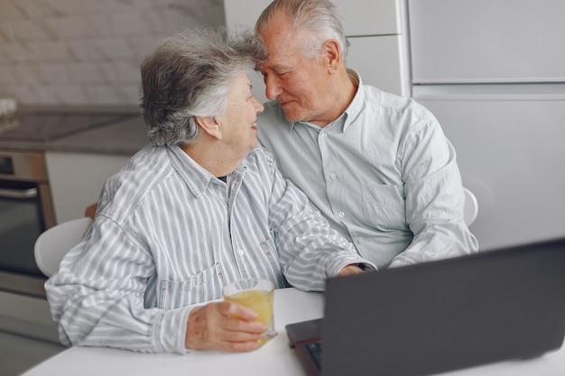 Elegancka stara para siedzi w domu i używa laptop