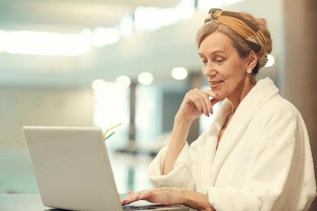 Elegancka starsza kobieta używa laptop pływackim basenem
