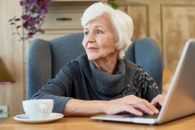 Elegancka starsza kobieta używa laptop