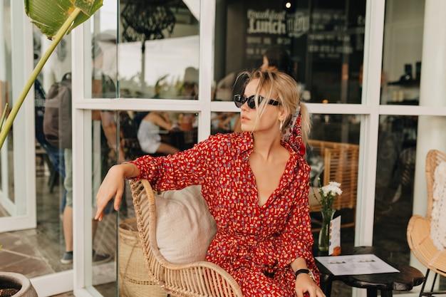 Elegancka stylowa pani siedzi w kawiarni na świeżym powietrzu i czeka na przyjaciół w dobry słoneczny dzień