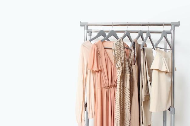 Elegancka sukienka, sweter, spodnie i inny modny strój w pastelowym beżowym kolorze. szafa domowa na wiosnę