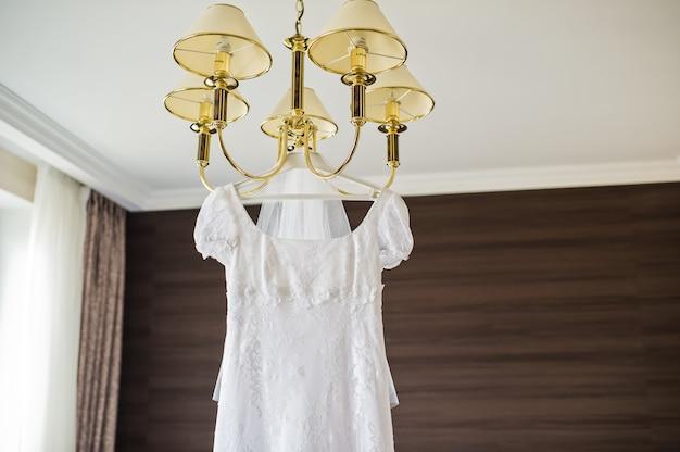 Elegancka suknia ślubna wisząca na żyrandolu we wnętrzu hotelu
