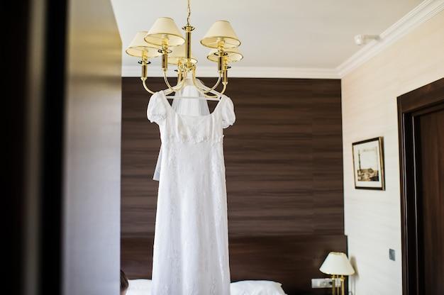 Elegancka suknia ślubna zawieszona na żyrandolu we wnętrzu hotelu