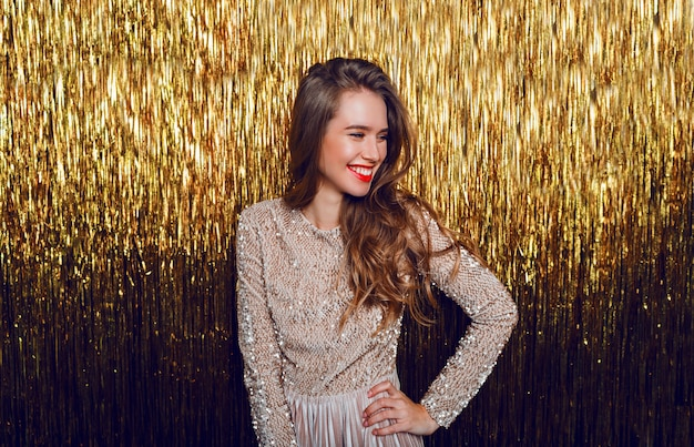 Elegancka świętująca kobieta z twarzą niespodzianki stojącej nad złotym musującym