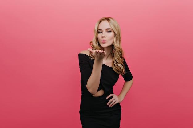 Elegancka, sympatyczna dziewczyna wysyłająca buziaka, pozując na różowej ścianie. zmysłowa romantyczna dama o kręconych blond włosach nosi stylową czarną sukienkę.