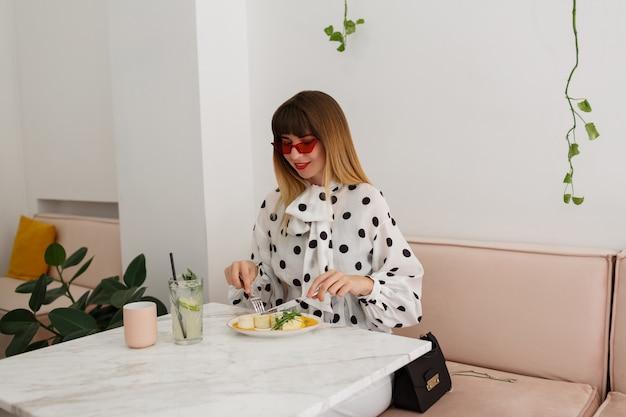Elegancka szczęśliwa kobieta je śniadanie w kawiarni