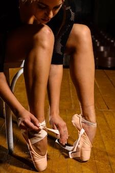 Elegancka tancerka baletowa zawiązująca pointe buty