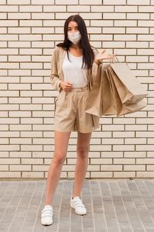 Elegancka ubrana kobieta trzyma torby na zakupy i ma na sobie maskę