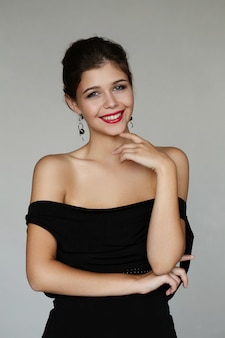 Elegancka urocza kobieta pozuje z czarną suknią