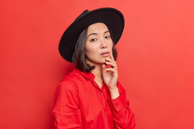 Elegancka urocza młoda azjatka trzyma rękę na brodzie z poważnym, pewnym siebie wyrazem ma naturalne ciemne włosy zdrowa skóra nosi czarny kapelusz czerwona koszula pozuje na jasnych