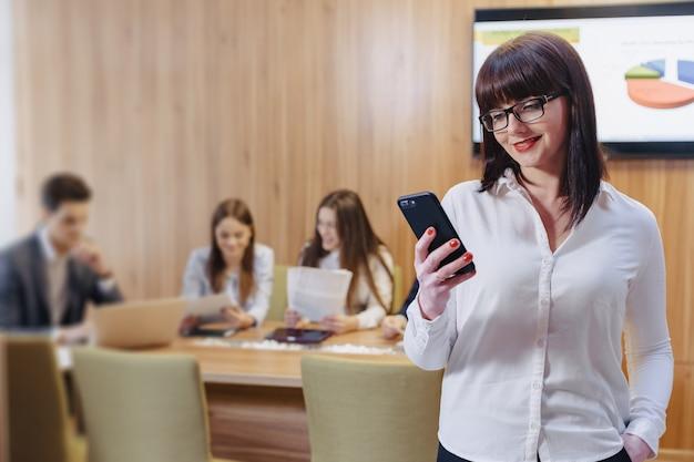 Elegancka urzędnik kobieta w szkłach z telefonem w rękach przeciw tłu pracujący koledzy