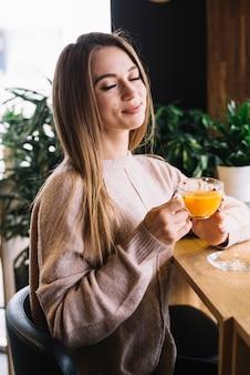 Elegancka zadowolona młoda kobieta trzyma filiżankę napój przy barem odpierającym w kawiarni