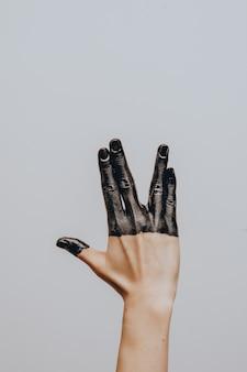 Elegancka żeńska ręka zanurzona w czarnej farbie. odosobniony. gest.
