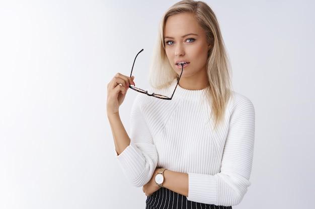 Elegancka, zmysłowa europejska jasnowłosa kobieta w stylowym swetrze gryzącym oprawkę okularów i wpatrująca się zalotnie z marzycielskim spojrzeniem w kamerę pozującą na białym tle, używając umiejętności uwodzenia.