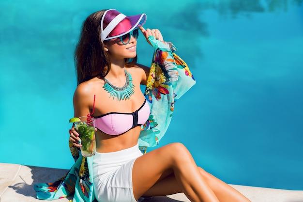 Elegancka, zmysłowa opalona kobieta w jasnych damskich wakacyjnych ubraniach siedzi przy dużym basenie i pije egzotyczny koktajl.