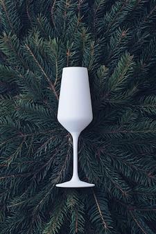 Elegancki biały flet szampański na tle zielonych gałęzi sosny tworzących ramę do wykorzystania jako szablon projektu na boże narodzenie, okres świąteczny lub uroczystość