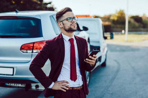Elegancki biznes człowiek w średnim wieku czeka na usługi holownicze o pomoc na drodze. koncepcja pomocy drogowej.