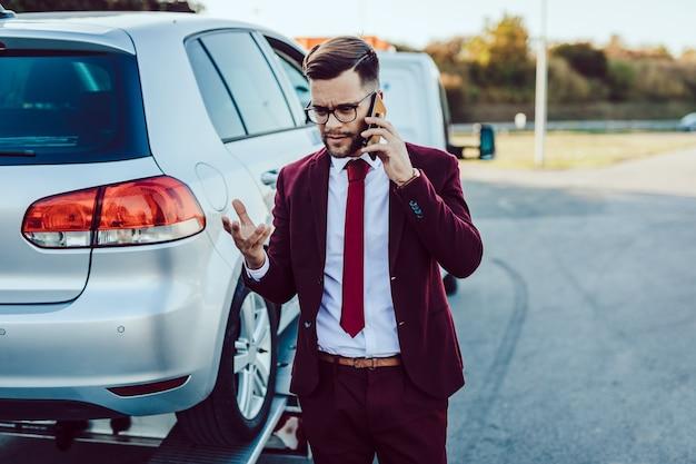 Elegancki biznes człowiek w średnim wieku dzwoniąc do usługi holowniczej o pomoc na drodze. koncepcja pomocy drogowej.