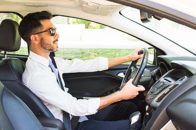 Elegancki biznesmen jest ubranym okulary przeciwsłonecznych jedzie samochód
