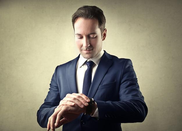 Elegancki biznesmen patrzeje jego zegarek