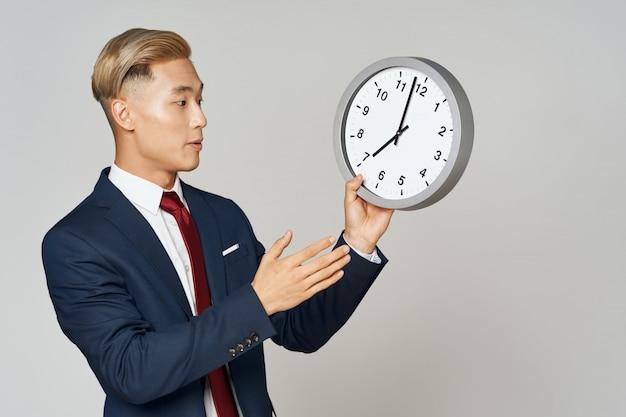 Elegancki biznesmen pozuje z zegarem