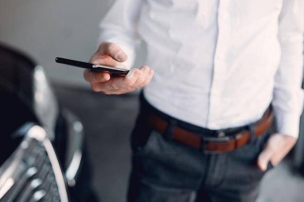 Elegancki biznesmen pracuje blisko samochodu