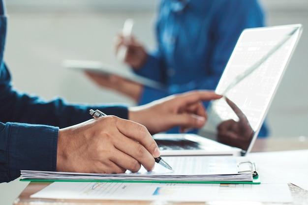 Elegancki biznesmen pracuje na swoim laptopie w biurze, analizuje dane i wykres, młody człowiek pisać na maszynie na komputerowym obsiadaniu przy drewnianym stołem.