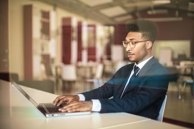 Elegancki biznesmen siedzi w sali konferencyjnej, pracując na swoim laptopie