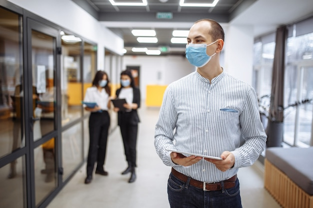 Elegancki biznesmen w masce medycznej stoi na korytarzu biura z tabletem w dłoniach.