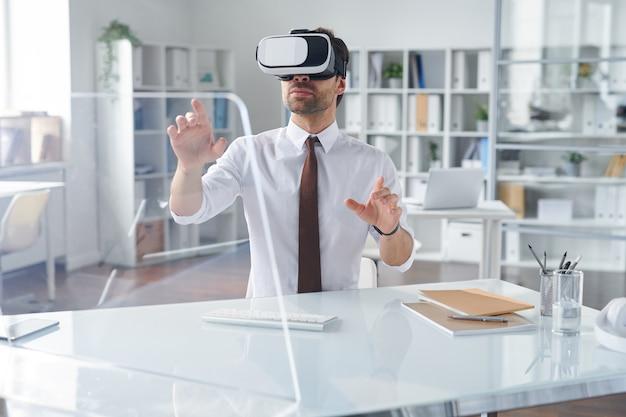 Elegancki biznesmen w zestawie słuchawkowym vr, wskazując na przezroczysty ekran komputera, siedząc przy biurku w biurze