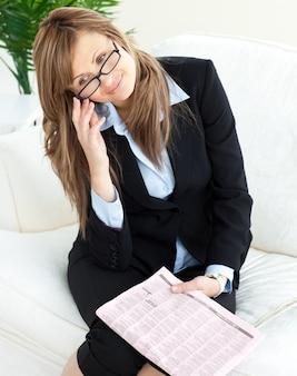 Elegancki bizneswoman trzyma gazetowego obsiadanie na kanapie