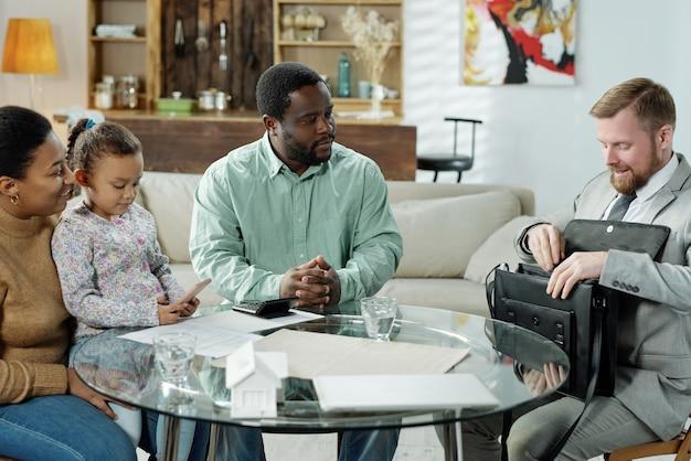 Elegancki brodaty mężczyzna odwiedzający rodzinę etniczną z małą dziewczynką, aby udzielić konsultacji hipotecznych