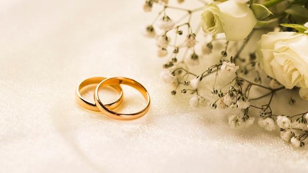 Elegancki bukiet kwiatów i pierścionki zaręczynowe