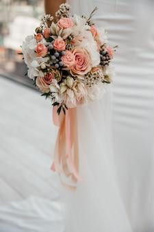 Elegancki bukiet ślubny w rękach panny młodej na białym