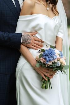 Elegancki bukiet ślubny ze świeżych naturalnych kwiatów i zieleni
