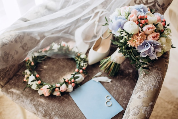Elegancki bukiet ślubny ze wstążką, zaproszenia ślubne, pierścionki zaręczynowe i buty dla panny młodej