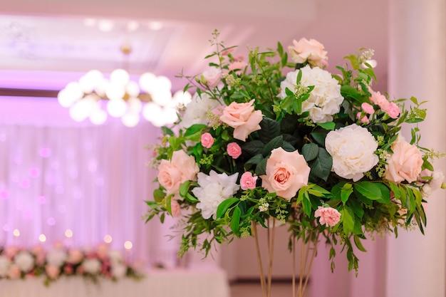 Elegancki centralny kwiatowy układ ślubny na pierwszym planie. koncepcja imprez weselnych. florystyka ślubna. luksus i piękno. ważne wydarzenia z życia. styl życia.