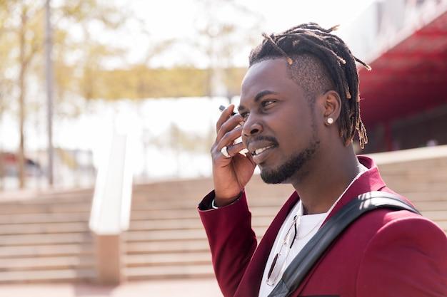 Elegancki czarny biznesmen słucha wiadomości głosowej na swoim smartfonie podczas spaceru po mieście, kopiuje miejsce na tekst, koncepcję technologii i komunikacji