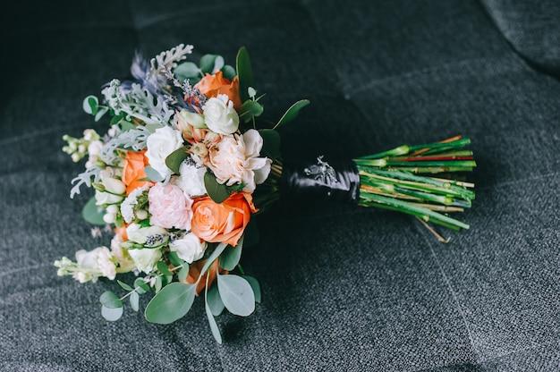 Elegancki delikatny bukiet panny młodej złożony z białych piwonii, hortensji, róż i gałązki zieleni leży na wygodnym fotelu w pokoju panny młodej. ścieśniać.