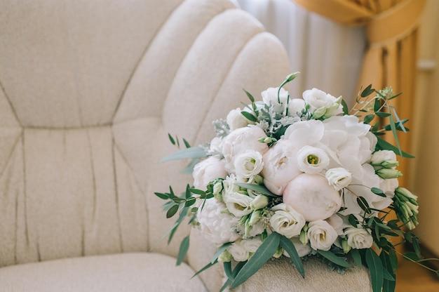 Elegancki delikatny bukiet panny młodej złożony z białych piwonii, hortensji, róż i gałązki zieleni leży na wygodnym fotelu w pokoju panny młodej.