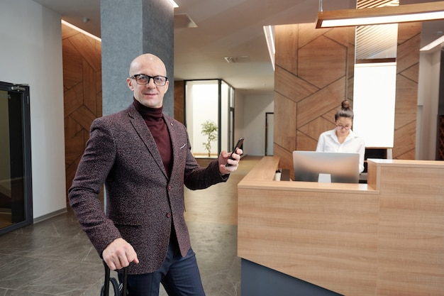 Elegancki dojrzały mężczyzna biznesowy podróżujący z walizką i smartfonem stojącym w hotelowym salonie pracującym recepcjonistą