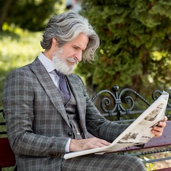 Elegancki dojrzały mężczyzna czyta gazetę na zewnątrz