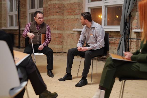 Elegancki dojrzały mężczyzna z laską siedzący na krześle obok innego pacjenta płci męskiej lub doradcy słuchającego go i udzielającego rad podczas sesji