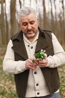 Elegancki dorosły mężczyzna w lesie wiosną