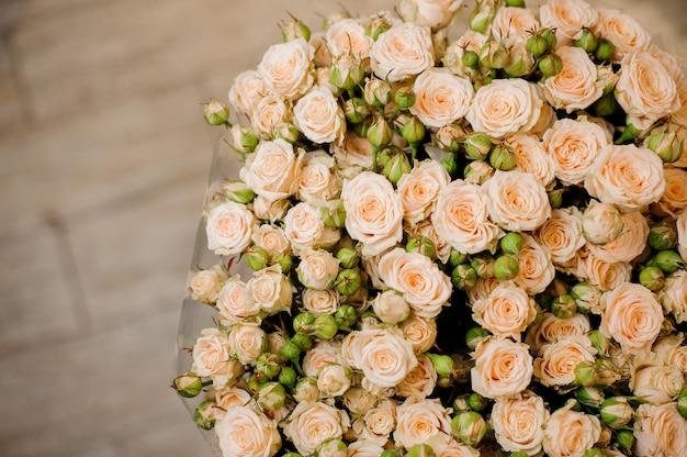Elegancki duży bukiet wielu małych róż w beżowym kolorze z bliska