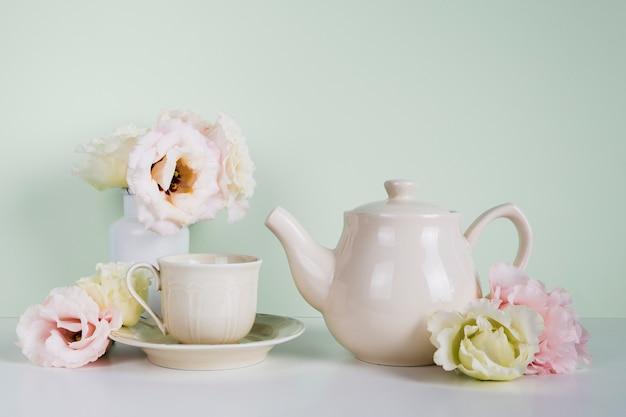Elegancki dzbanek do herbaty obok kwiatów