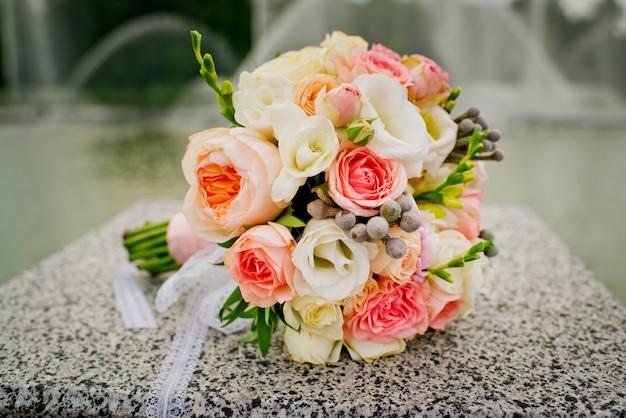Elegancki i piękny bukiet ślubny na tle fontann