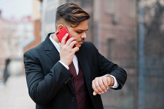 Elegancki indyjski biznesmen w formalnej odzieży pozyci przeciw okno w centrum biznesu. patrzy na zegarki i rozmawia przez telefon.